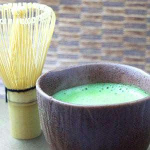 Matcha in bowl with crema and bamboo whisk from KenkoTea