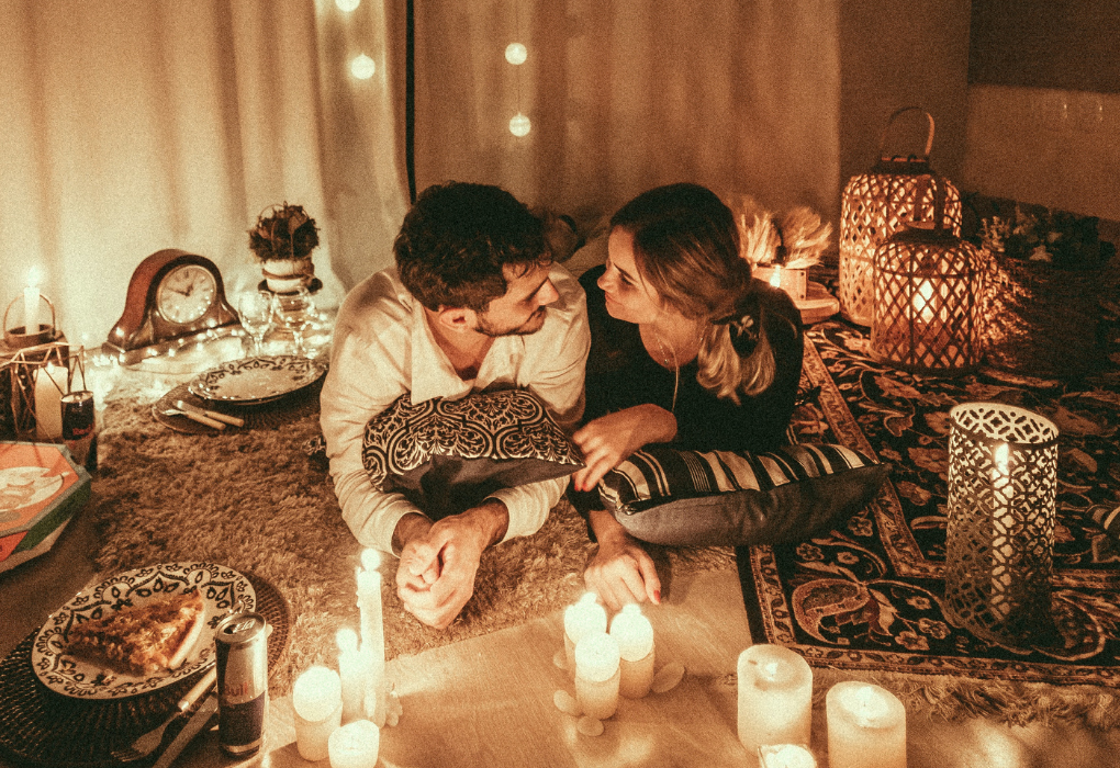 A couple looking at each other with cozy candles around them
