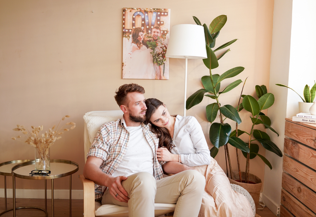 A couple sitting on sofa, with a fiddle leaf plant and a lamp on their side. A coffee table on the right