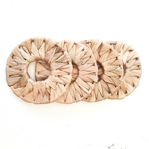 Rounded natural seagrass coasters for protecting table surfaces.