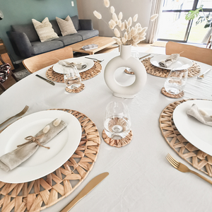Woven placemats styled to create a boho dining table with pampas grass, nordic vase, and gold utensils
