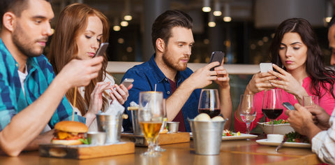 education standing desk provider shows photo of people using phones at the dinner table