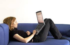 Young woman sat on sofa using laptop