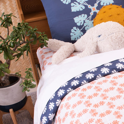 Angled view of single bed with Kikau's Coconut White kids sheet and Pacific Ocean Blue pillowcase and quilt cover