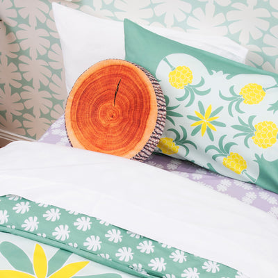 Angled view of single bed with Kikau's Coconut White kids sheet and Pineapple Paradise Green pillowcase and quilt cover