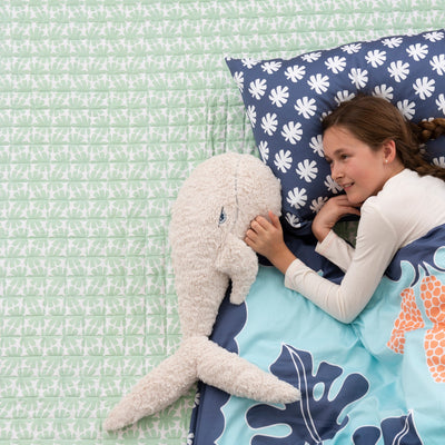 Bird's eye view of girl lying on Kikau's Coral and Green Coco Palm Quilted Bedspread with her toy whale, a Pacific Ocean Blue quilt cover is on top of her