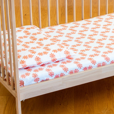 Angled view of cot bed with Kikau's Coral Orange Coco Palm printed sheet and toddlers pillowcase