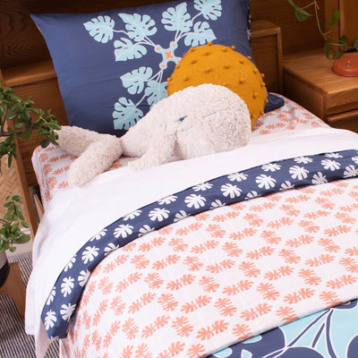 Angled view of single bed with Kikau's Coral Orange Coco Palm printed sheet and Pacific Ocean Blue kids quilt cover set