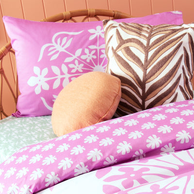 Angled view of single bed with Kikau's Palm Green Coconut Palm printed sheet and Fruity Frangipani Pink kids pillowcase