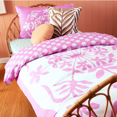 Birds eye view of single bed with Kikau's Palm Green Coconut Palm printed sheets and Fruity Frangipani Pink kids quilt cover set