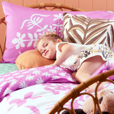 Young girl lying on single bed with Kikau's Palm Green Coconut Palm printed sheets and Fruity Frangipani Pink kids quilt cover set
