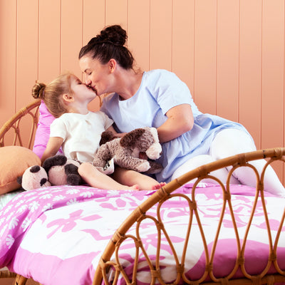 Mother and daughter kissing each other on single bed with Kikau's Fruity Frangipani Pink kids quilt cover set