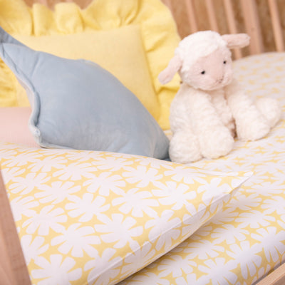 Angled view of cot bed with Kikau's Lemon Yellow Coconut Palm printed sheet and toddlers pillowcase with toy lamb sitting on it