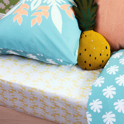 Angled view of single bed with Kikau's Lemon Yellow Coconut Palm printed sheet and Sea Foam Green kids pillowcase
