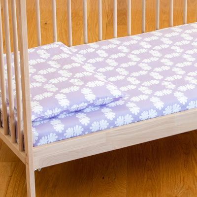 Angled view of cot bed with Kikau's Lots of Lilac Coconut Palm printed sheet and toddlers pillowcase