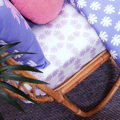 Angled view of single bed with Kikau's Lovely Lilac Coco Palm printed sheet and Wild Bird-of-Paradise Lilac kids quilt cover