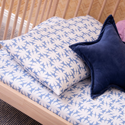 Angled view of cot bed with Kikau's Ocean Blue Coco Palm printed sheet and toddlers pillowcase