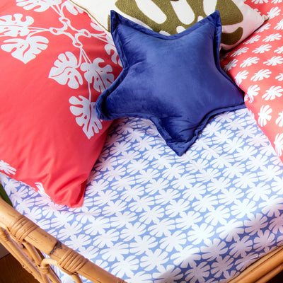 Angled view of single bed with Kikau's Ocean Blue Coco Palm printed sheet and Tropical Raro Red kids pillowcase