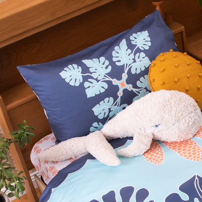 Angled view of single bed with Kikau's Coral Orange Coconut Palm printed sheet and Pacific Ocean Blue kids pillowcase