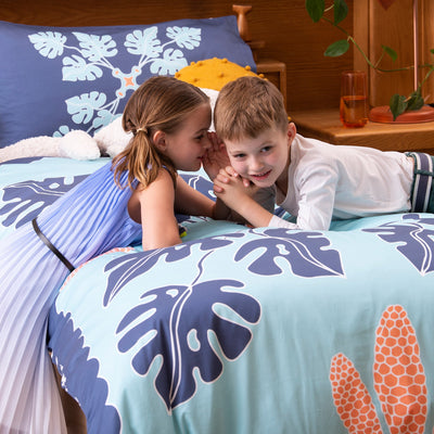 Brother and sister whispering secrets to each other on single bed with Kikau's Pacific Ocean Blue kids quilt cover set