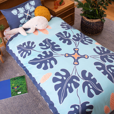 Birds eye view of single bed with Kikau's Coral Orange Coconut Palm printed sheets and Pacific Ocean Blue kids quilt cover set