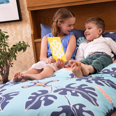 Brother and sister reading together on single bed with Kikau's Pacific Ocean Blue kids quilt cover set