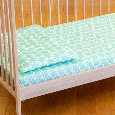 Angled view of cot bed with Kikau's Palm Green Coco Palm printed sheet and toddlers pillowcase