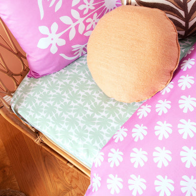 Angled view of single bed with Kikau's Palm Green Coco Palm printed sheet and Fruity Frangipani Pink kids pillowcase