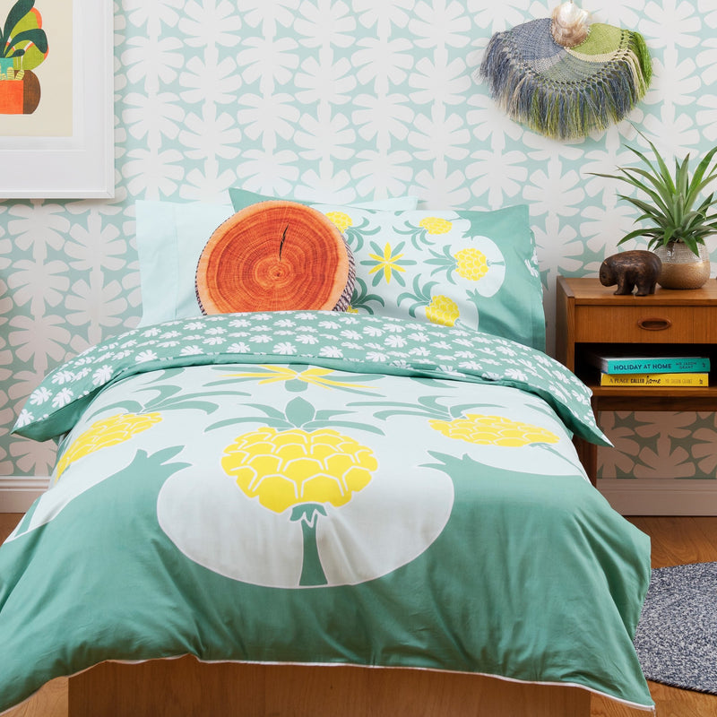 Mum and son looking at footy cards together on single bed with Kikau's Pineapple Paradise Green kids quilt cover set
