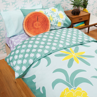 Angled view of single bed with Kikau's Lots of Lilac Coconut Palm printed sheets and Pineapple Paradise Green kids quilt cover set