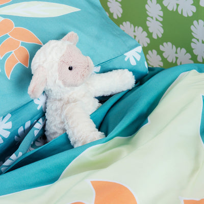 Birds eye view of single bed with Kikau's Lemon Yellow Coconut Palm printed sheets and Sea Foam Green kids quilt cover set with lamb toy in pocket