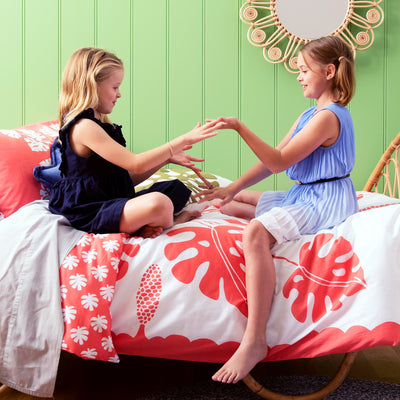 Sisters playing hand games together on single bed with Kikau's Tropical Raro Red kids quilt cover set
