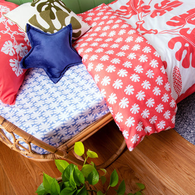 Birds eye view of single bed with Kikau's Ocean Blue Coconut Palm printed sheets and Tropical Raro Red kids quilt cover set