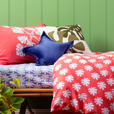 Side view of single bed with Kikau's Ocean Blue Coconut Palm printed sheets and Tropical Raro Red kids quilt cover set