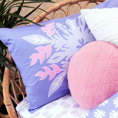 Angled view of single bed with Kikau's Lovely Lilac Coconut Palm printed sheet and Wild Bird-of-Paradise Lilac kids pillowcase