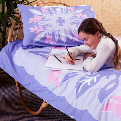 Girl colouring in her book, lying on top of single bed with Kikau's Wild Bird-of-Paradise Lilac kids quilt cover set