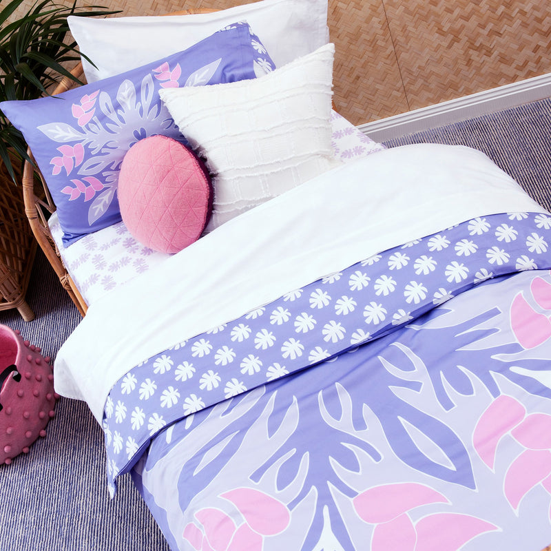 Mother and daughter reading together on single bed with Kikau's Wild Bird-of-Paradise Lilac kids quilt cover set
