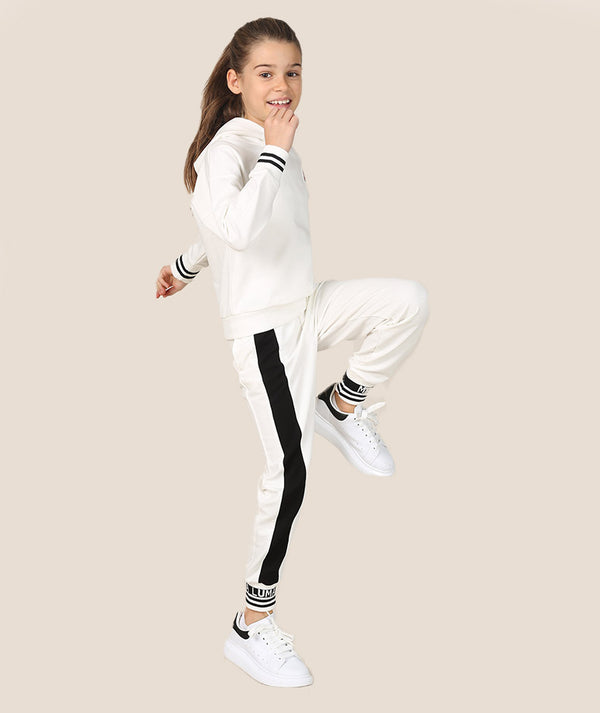 Girl in white and black athleisure tracksuit by Mama Luma