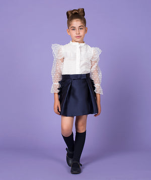 Girl in designer outfit featuring a white blouse with sheer sleeves and pleated navy blue skirt by Mama Luma