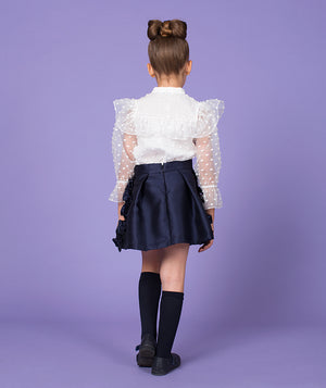 Back of girl in white sheer blouse and navy blue pleated skirt