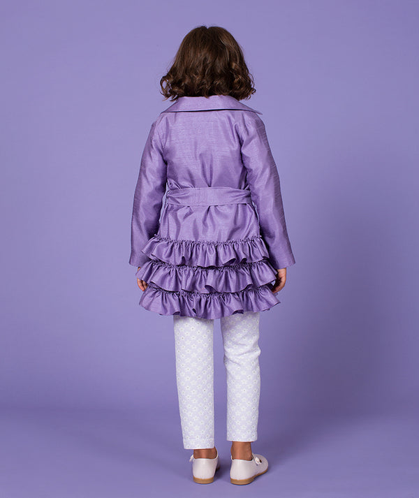 Back of girl in purple designer coat with ruffles for kids and white daisy pants by Mama Luma