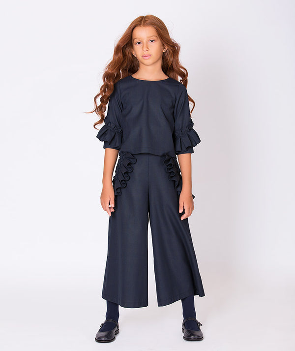 Girl in navy blue ruffle blouse and navy blue ruffle dress pants for girls by Mama Luma