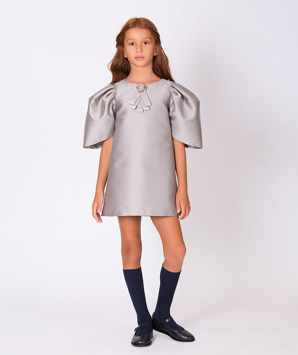 Girl in gray taffeta dress with puffy shoulders and brooch for kids