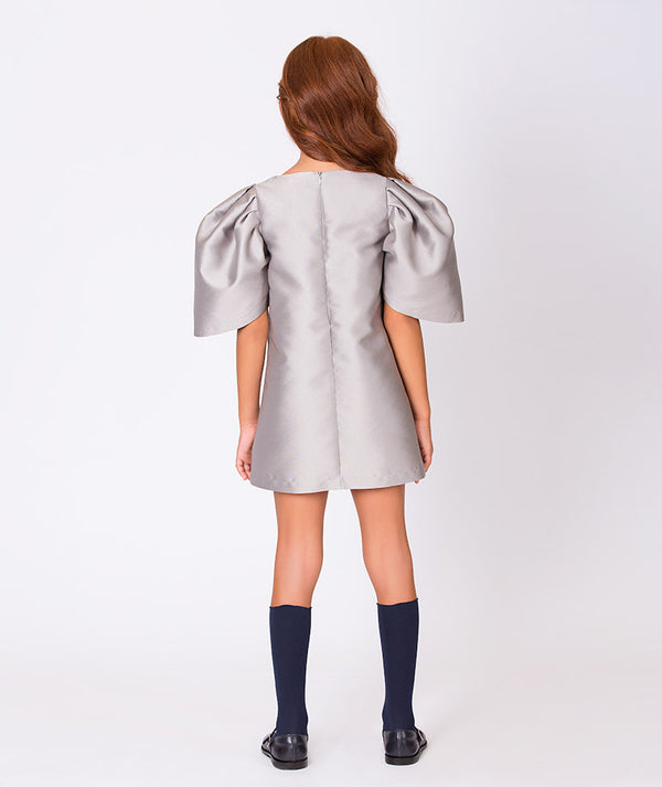 Back of girl in gray taffeta dress with puffy shoulders and brooch for kids