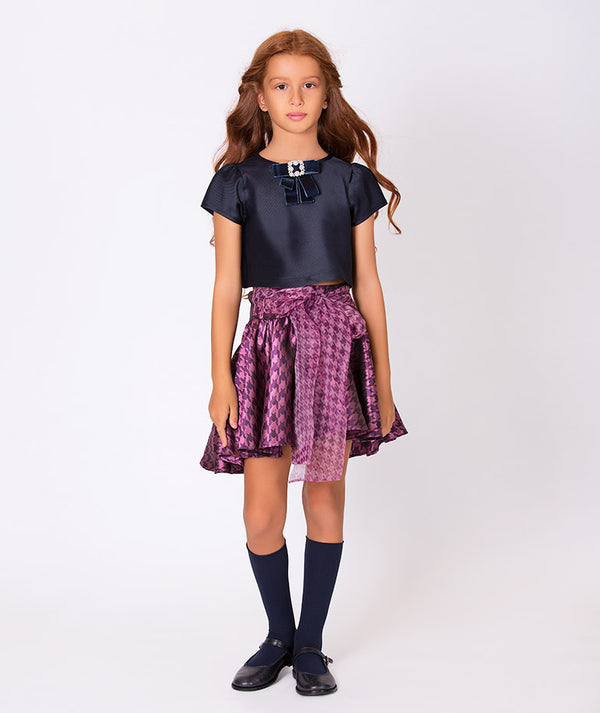 Girl in chic navy blue blouse for kids and jacquard purple skirt with big bow for children