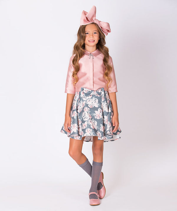 Girl in shiny pink blouse, gray and pink flower print skirt and big pink bow for girls