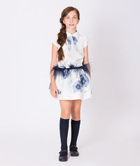 Girl in two piece outfit: white collared blouse for kids with blue textured tie and white skirt for girls with blue flower print and blue feathers