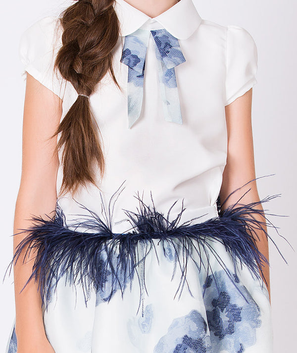 Two piece outfit: white collared blouse for kids with blue textured tie and white skirt for girls with blue flower print and blue feathers