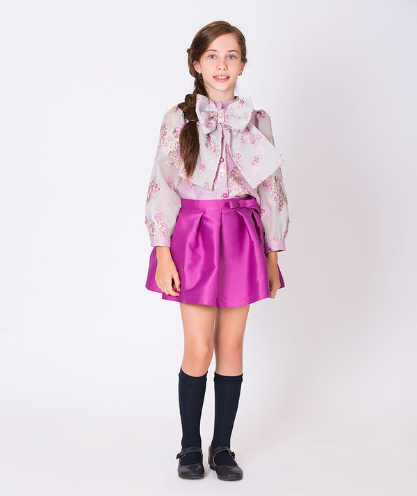 Girl in sheer blouse with lilac flowers and big bow and pleated taffeta lilac skirt for kids