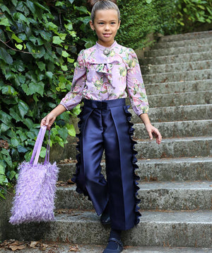 Girl in floral blouse ruffle designer pants for kids and furry chic bag